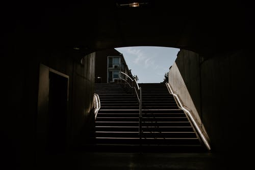Empty tunnel of underground passage in shade and stone stairs with metal railings
