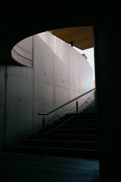 Long thin railing and staircase by tall grey wall to underground passage in daytime