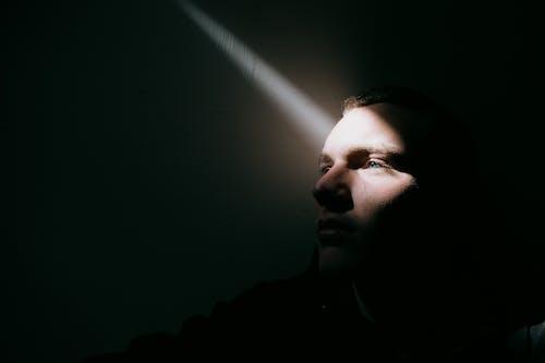 Unemotional man in dark room in sunbeam