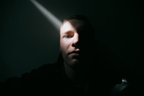 Pensive young male with short hair thoughtfully looking at camera by wall in dark room in sunlight