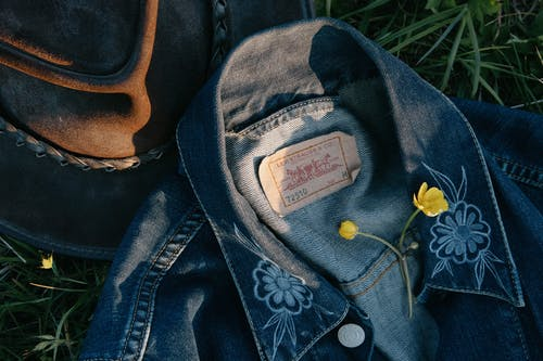 Top view of small yellow fragile flower on denim jacket near hat on green grass in daytime