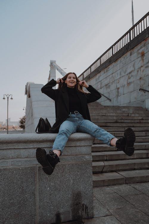 Беззаботная женщина в модной одежде на заборе возле городской лестницы