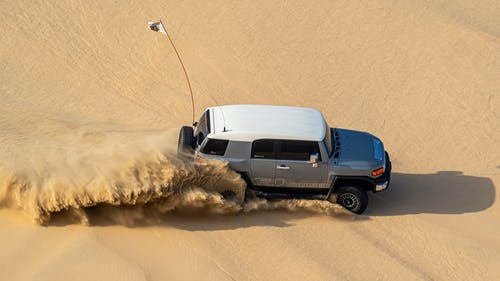Modern SUV driving in sand of desert on hot day