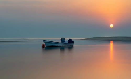 Picturesque scenery of tranquil river with moored boat in orange shiny sunset in evening