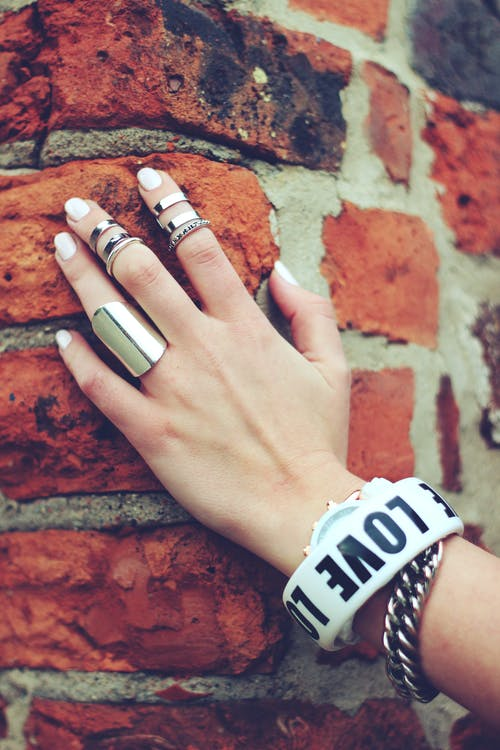 Hand on the bricks with multiple rings in different finger, and stacking rings