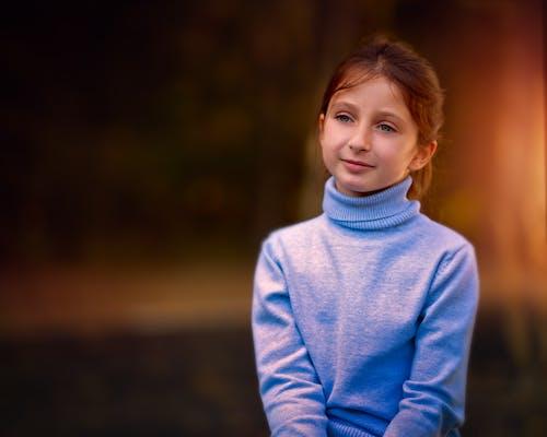 Cute little girl in warm turtleneck in nature