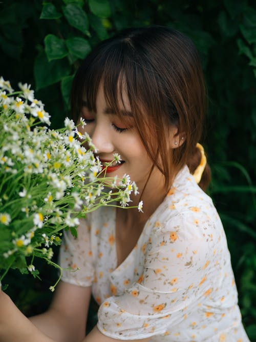Happy Asian woman smelling blooming flowers