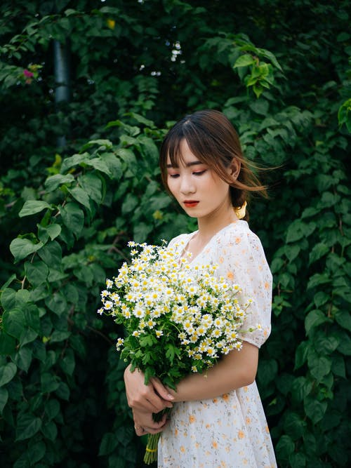 Side view of attractive young female standing with closed eyes and holding bouquet of blooming flowers near shrubs