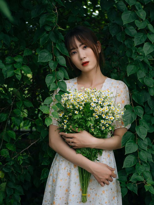Young female in summer dress holding bouquet of fresh flowers and looking at camera