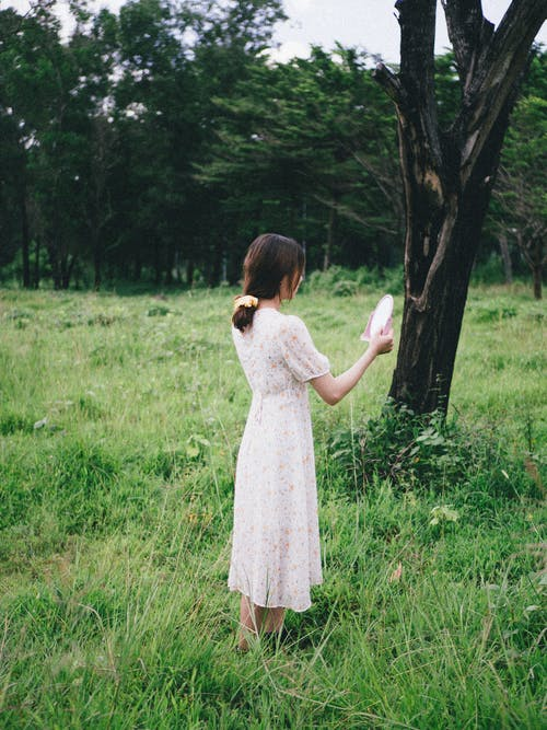 Faceless woman with mirror in field