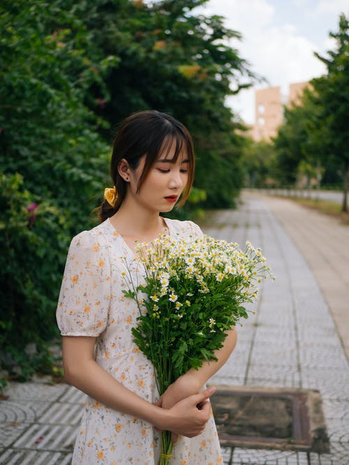 Young female in casual dress holding bouquet of fresh flowers and looking down while standing in park