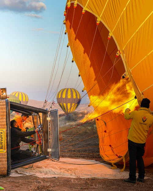 Group of people making fire and launching colorful hot air balloons in clear sky