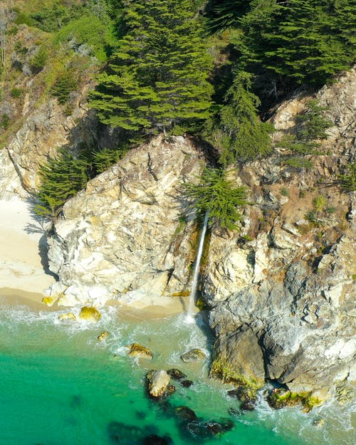 Aerial view of rough rocky coast with turquoise sea water and green tropical plants