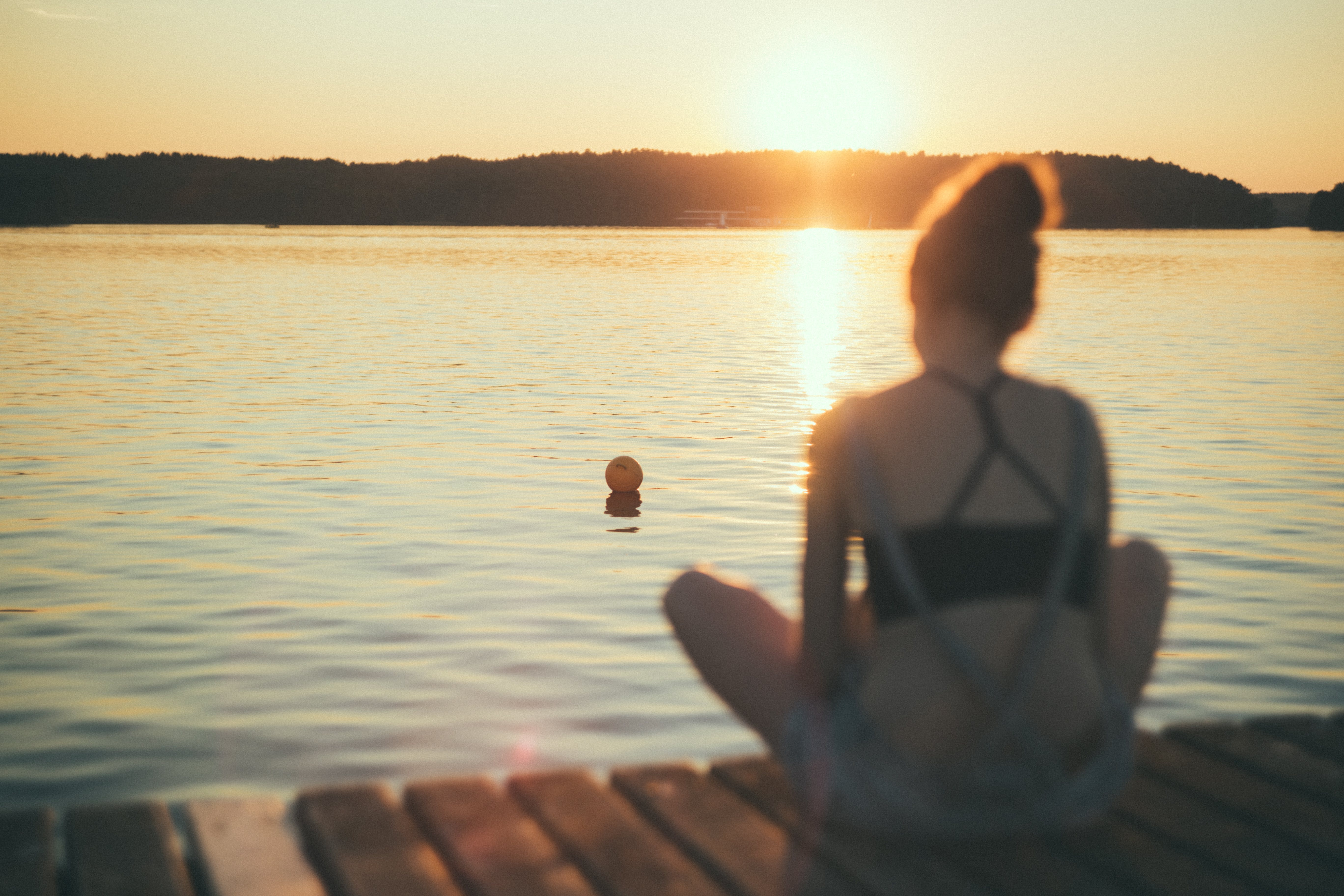 Woman Sitting on Dock Staring at the Ball