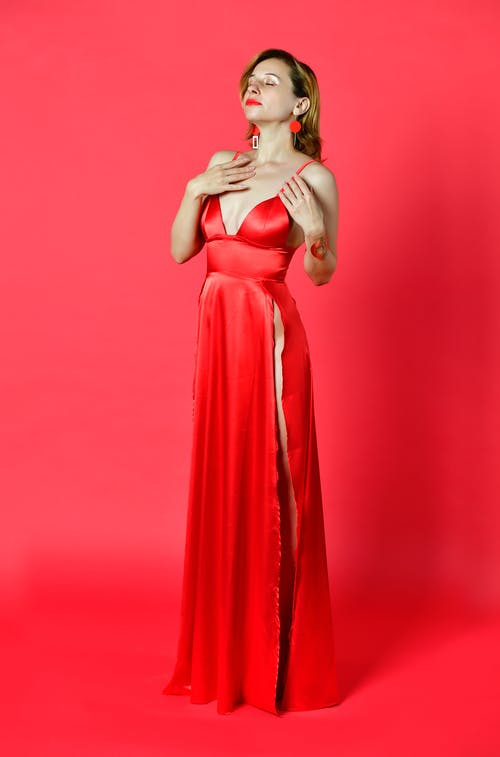 Young dreamy woman in stylish dress touching chest with closed eyes while standing on red background