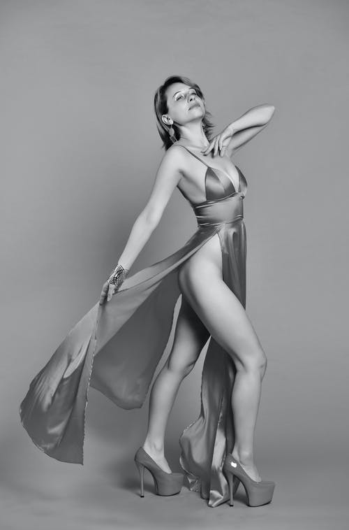 Side view of black and white sensual young female model in provocative dress and high heeled shoes standing in studio with closed eyes