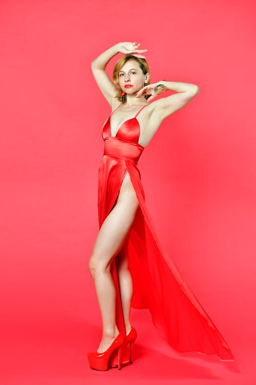 Alluring young lady in provocative dress standing in red studio with raised arms
