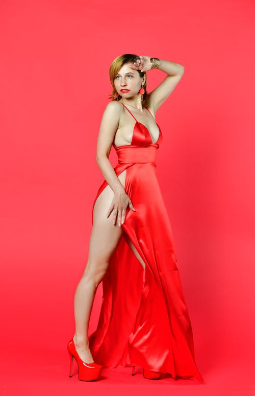 Gorgeous young lady in red dress with slit standing in studio and looking away