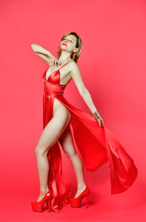 Side view of young confident alluring woman in sexy red dress with slit standing in bright studio and looking away