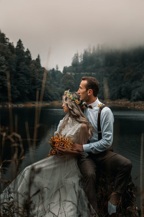 Young groom gently embracing bride with flower wreath and bouquet while sitting on river shore against woods and looking away