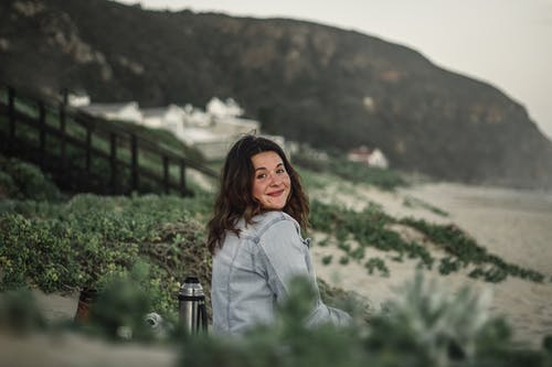 Side view of satisfied lady in jean jacket sitting on sandy seacoast with thermos near greenery and smiling while looking at camera over shoulder in overcast day