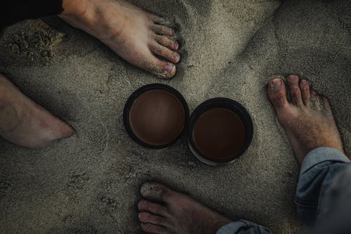Top view of crop unrecognizable barefoot couple of travelers standing on sandy coast hot drinks in thermos lids in overcast day