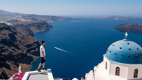 Man in White T-shirt Standing on White Concrete Building Near Blue Sea