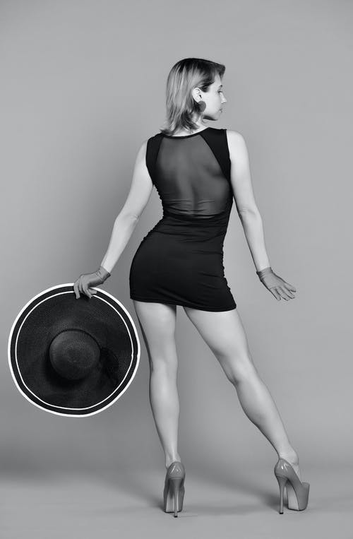 Back view of black and white confident young woman with perfect body in mini dress and high heels standing in studio with hat in hand and looking away