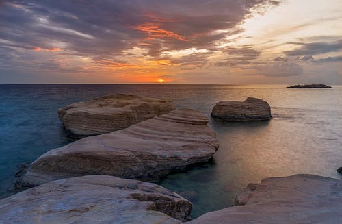 Spectacular scenery of rocks placed in rippling water of ocean under colorful cloudy sky at sunrise