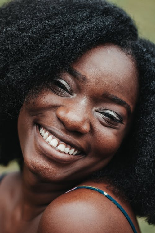 Happy adult African American female with perfect skin smiling while looking at camera