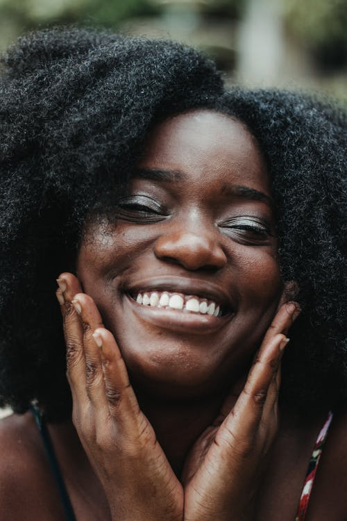 Charming African American female with curly hair smiling and touching cheeks on blurred background