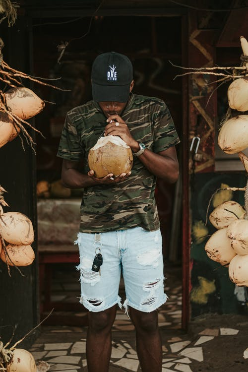 African American male wearing casual outfit drinking fresh coconut water standing near entrance of house