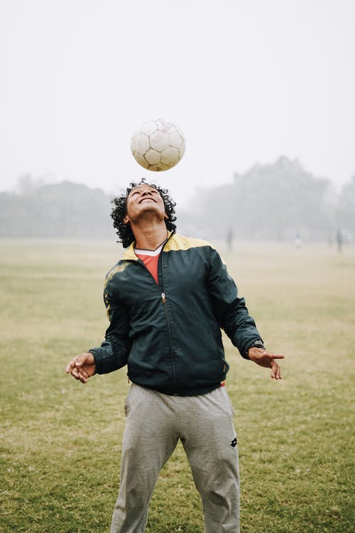 Smiling football male player with curly hair wearing sportswear hitting soccer ball with head while playing on field