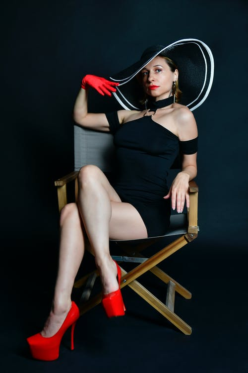 Full body of young sensual female model in elegant mini dress and high heels resting on chair with crossed legs and touching hat against black background