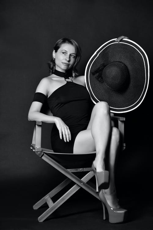 Black and white of confident stylish lady in mini dress and high heels with hat in hand resting on chair in dark studio and looking away