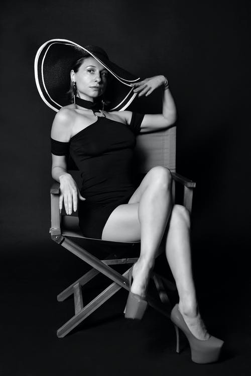 Fashionable young young female model resting on chair in studio