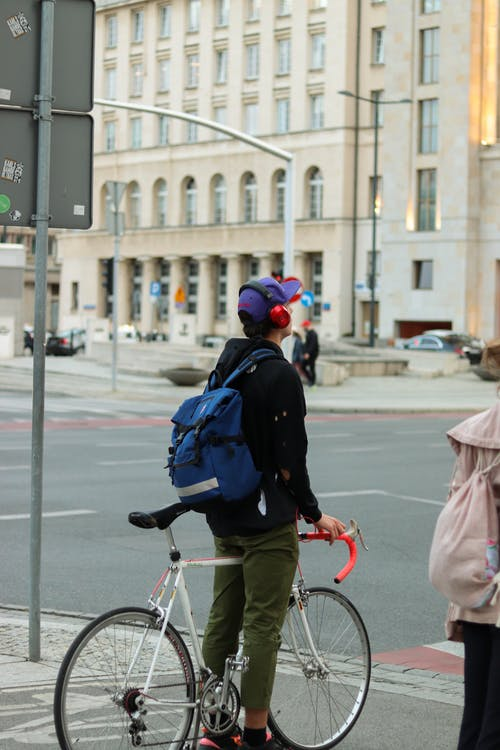 Unrecognizable man with bicycle standing near crosswalk