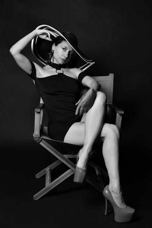 Confident young woman in elegant outfit sitting on chair
