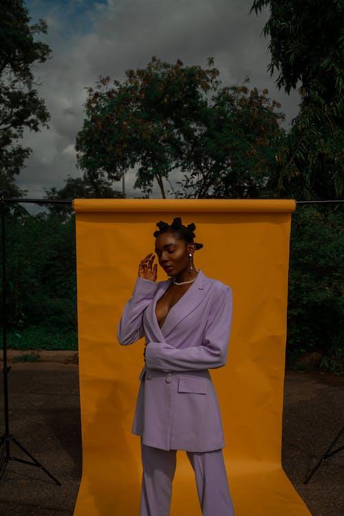 Black woman standing on orange background