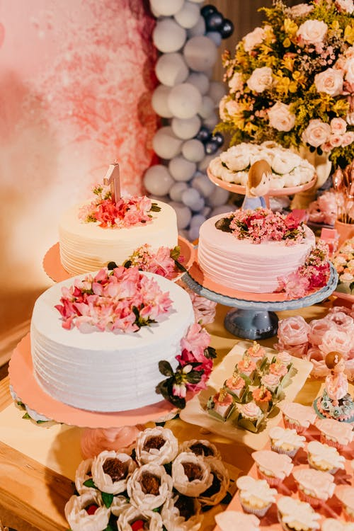 High angle of delicious sweet cakes decorated with flowers near appetizing desserts on wedding party