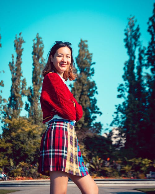 Woman in Red and Blue Plaid Skirt And Red Crop Top Standing Near Green Trees
