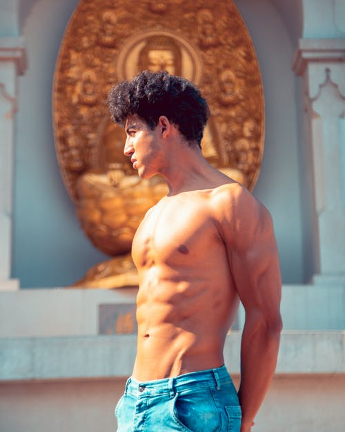 Shirtless Man in Blue Denim Pants Standing Near A Budhha Shrine