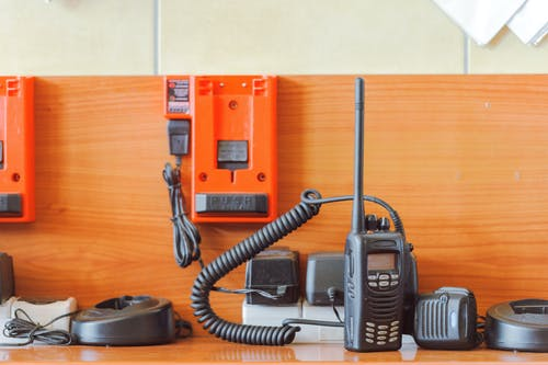 Walkie talkie on table near wooden wall with charge rack