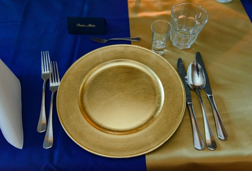 Empty golden plate with cutlery and glassware served on table