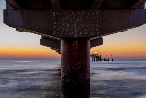 Long pier over ocean at sunset