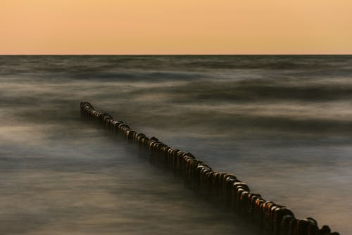 Tetrapods in wavy sea at sunset