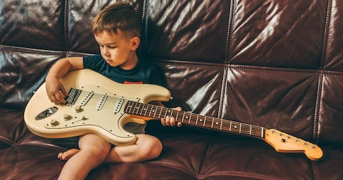 Boy in Red Crew Neck T-shirt Playing White and Black Stratocaster Electric Guitar