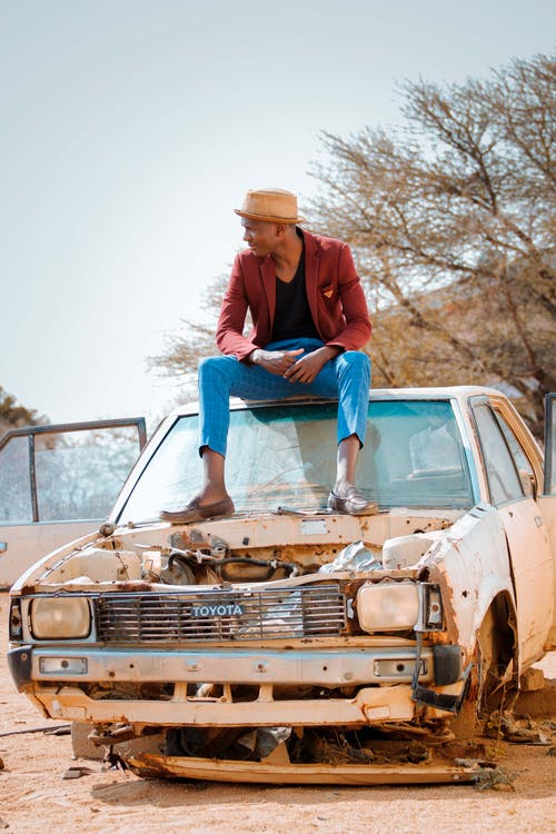 Full body of young trendy ethnic male in stylish blazer and hat sitting on roof of old broken car and looking away