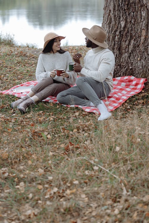 Man And Woman Sitting on Red and White Textile On A Grass Field