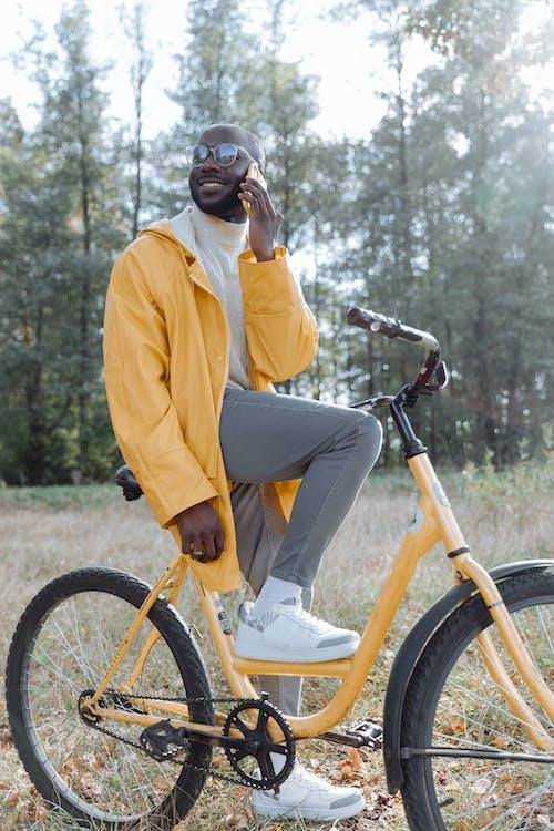 Homem Com Manto Amarelo Andando De Bicicleta No Campo De Grama Verde
